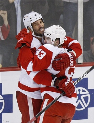 Andreas Lilja hugs Darren Helm after a Helm's shorthanded goal.